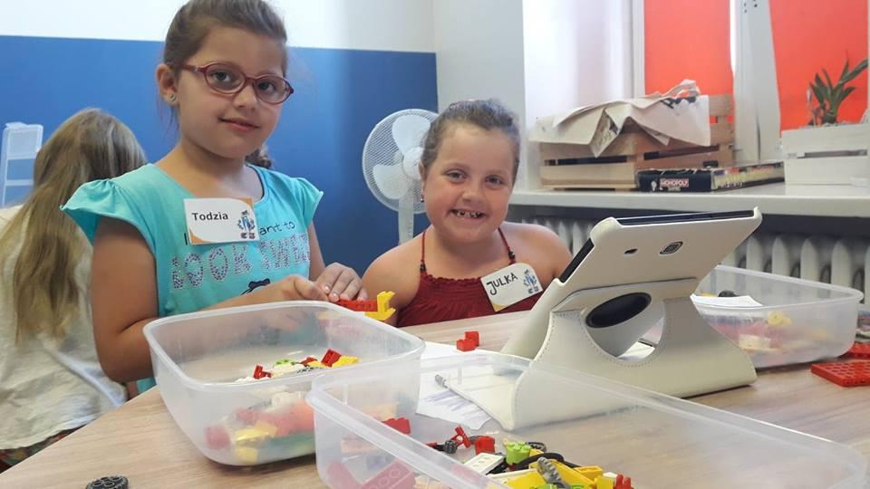 Obraz przedstawia naszych wychowanków podczas warsztatów z robotyki. Na zdjęciu możemy ujrzeć budowę robota oraz tablet dzięki któremu możemy zaprogramować robota.