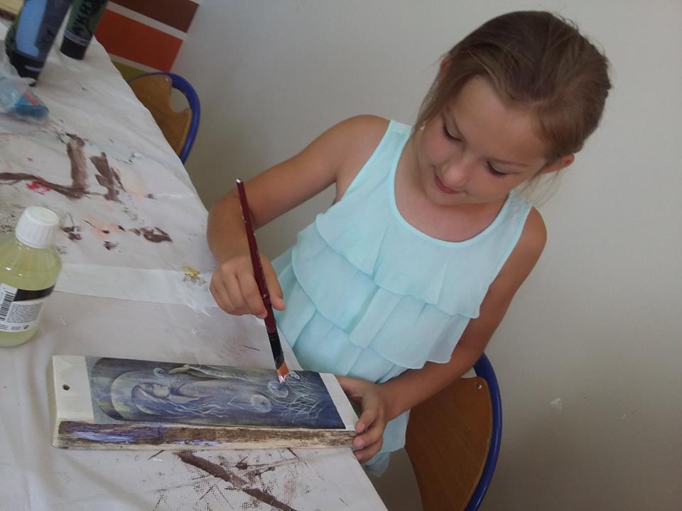 Zdjęcie przedstawia dziewczynkę malującą coś na drewnie. Stół jest przykryty białym obrusem.