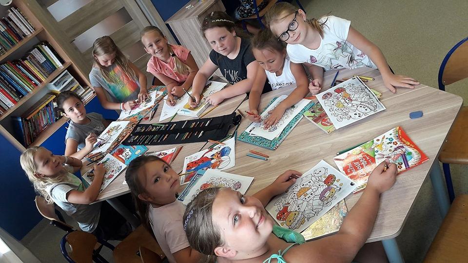 Obraz przedstawia wychowanków SPWD podczas wakacyjnych zajęć artystycznych. Na zdjęciu dzieci malują różnego rodzaju kolorowanki przy użyciu kredek.