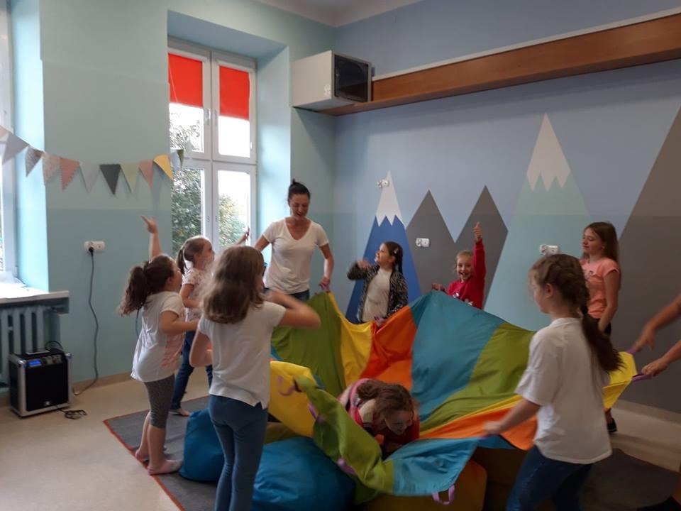Obraz przedstawia zajęcia socjoterapeutyczne. Na zdjęciu możemy ujrzeć wychowanków podczas różnego rodzaju zabaw związanych z socjoterapią.