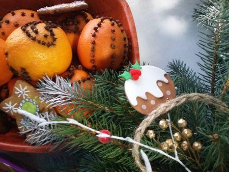 Zdjęcie przedstawia gałązkę choinki oraz ręcznie wykonane dekoracje świąteczne.