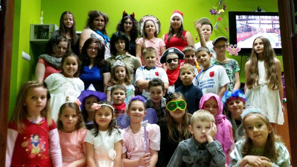 Zdjęcie przedstawia dzieci z placówki ustawione do zdjęcia podczas zabawy sylwestrowej w placówce.