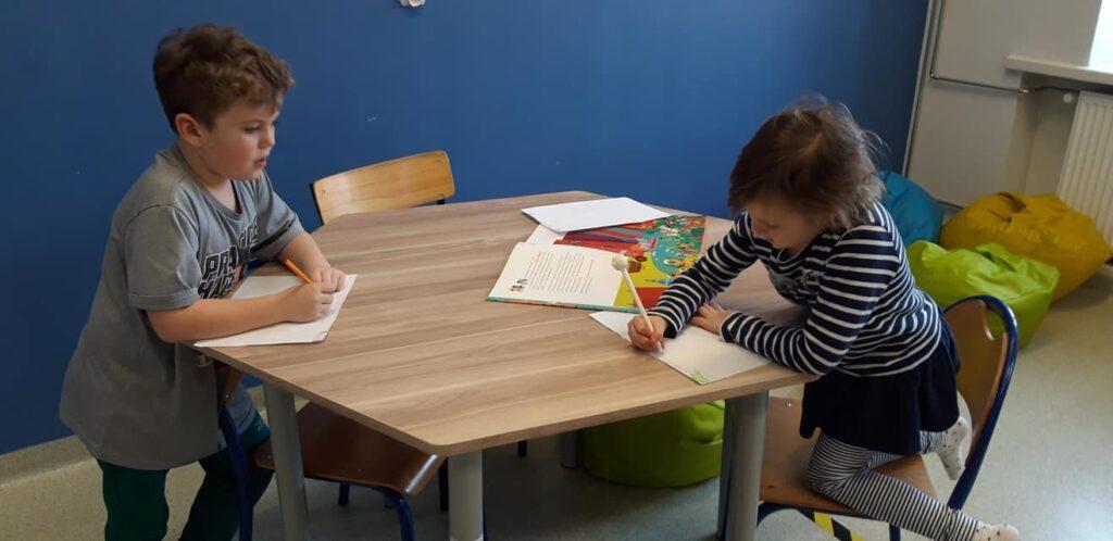 Obraz przedstawia dwójkę dzieci wypełniające karty pracy.