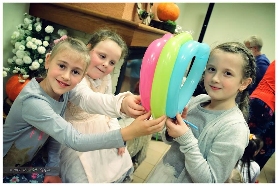 Zdjęcie przedstawia dzieci trzymające przedmioty w kształcie serc w kolorach różowym, żółtym i niebieskim.
