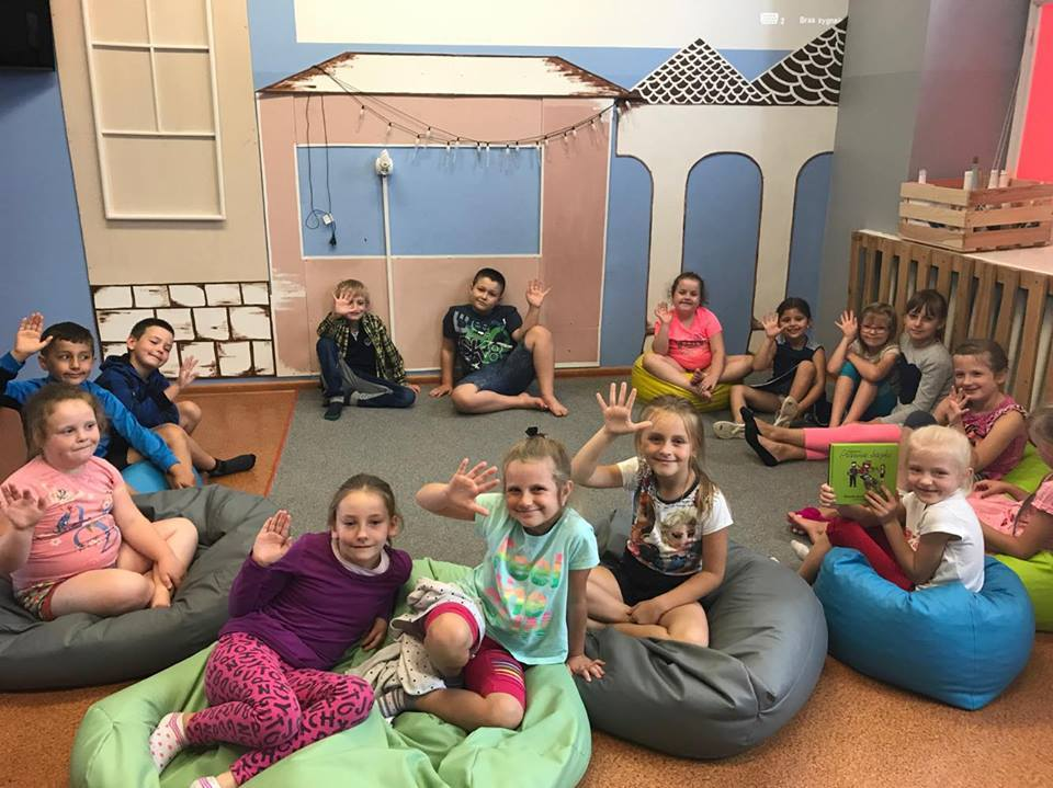 Zdjęcie przedstawia dzieci siedzące na specjalnych rzeczach do siedzenia w pokoju z niebieskimi ścianami oraz dekoracją w kształcie domku.