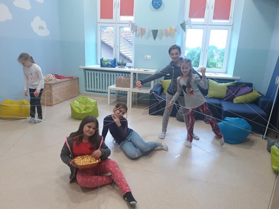 Obraz przedstawia wychowanków SPWD podczas zabaw, gdy na zewnątrz pada deszcz. Na zdjęciu możemy ujrzeć dzieci bawiące się na torze przeszkód wykonanym z włóczek.
