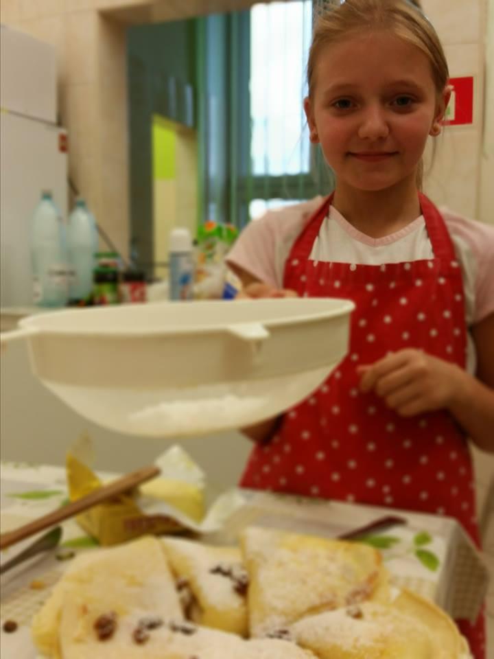 Zdjęcie przedstawia dziewczynkę z placówki kończącą dekorację ciasta.