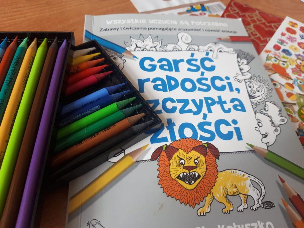 Obraz przedstawia kredki oraz kolorowanki.
